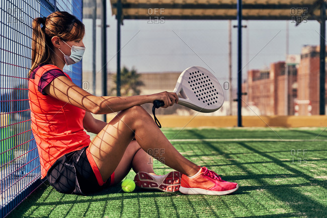 Side view of female player in medical mask sitting with racket and ball on sports ground for paddle tennis during coronavirus epidemic
