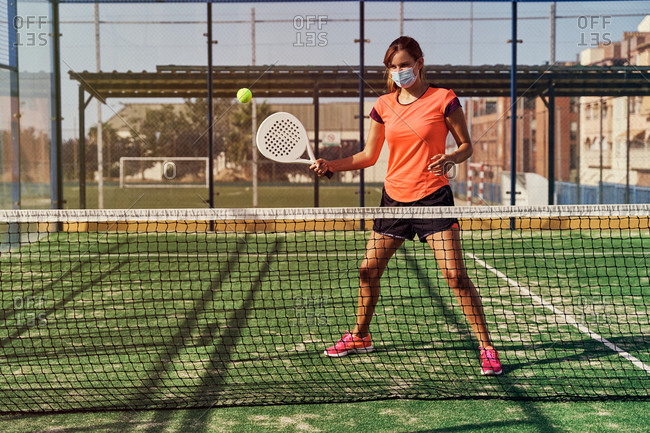 Focused sportswoman in activewear and mask with racket playing paddle tennis on sports ground in summer