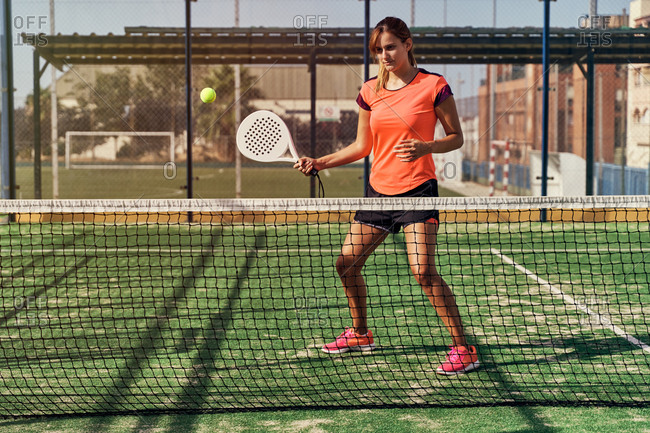 Focused sportswoman in activewear and with racket playing paddle tennis on sports ground in summer
