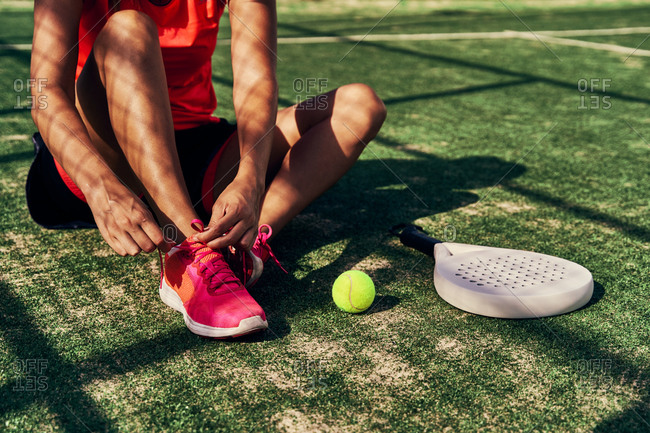 Crop female paddle tennis player sitting on court and tying shoelaces before training