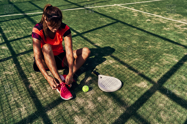 High angle of serious female paddle tennis player sitting on court and tying shoelaces before training