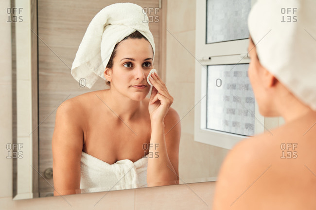 Charming female in towel turban standing in bathroom in front of mirror and treating face with cotton sponge