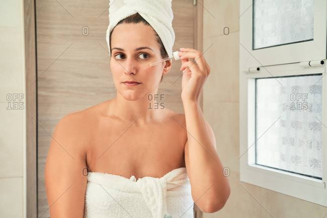 Calm female with pipette applying facial serum on smooth skin while standing in towel turban in bathroom at home and looking in mirror