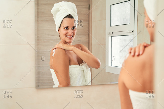 Content female in towel turban standing in front of mirror and smearing moisturizing body lotion on arm after shower