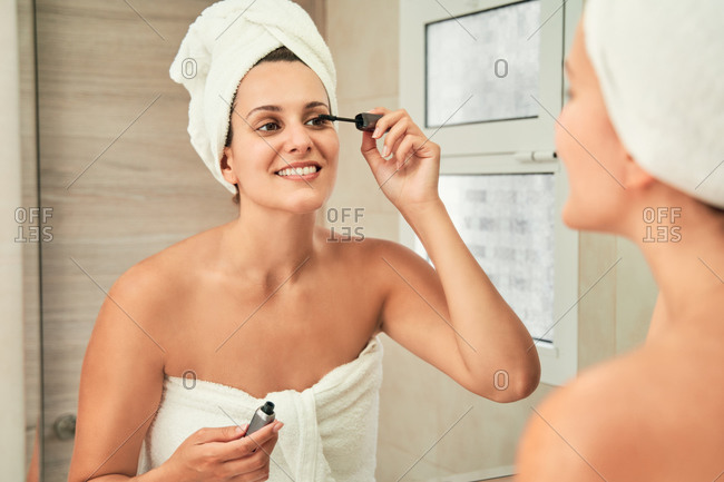 Charming female looking in mirror and applying mascara on eyelashes while standing in towel turban in bathroom after shower