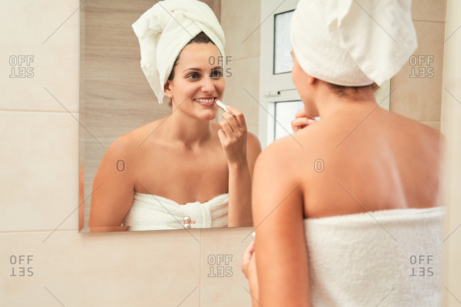 Delighted female in towel turban standing in bathroom and applying lipstick in front of mirror