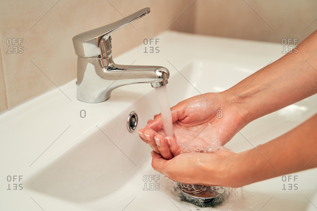 Unrecognizable crop female washing hands in sink under fresh water in modern bathroom