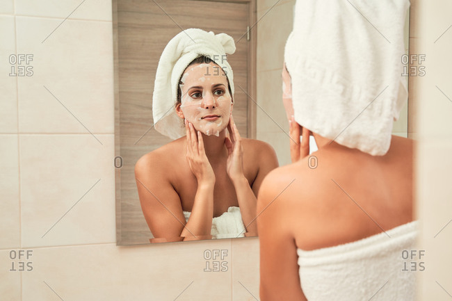 Focused female in towel turban applying moisturizing mask on face while standing in front of mirror after shower in bathroom