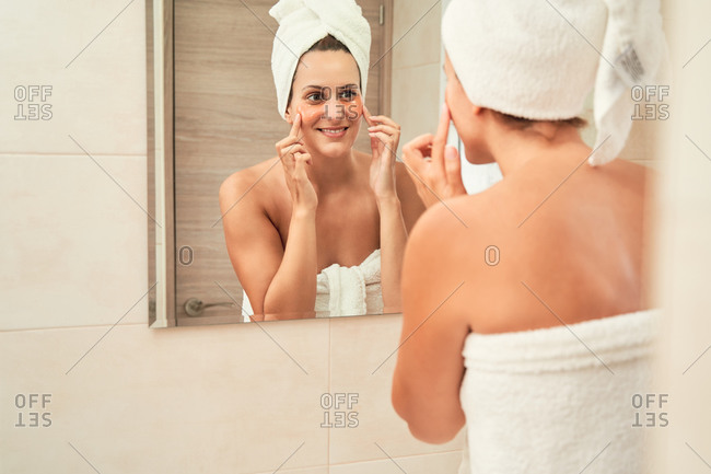 Tender female in towel turban looking in mirror and smearing facial cream while moisturizing skin and standing in bathroom