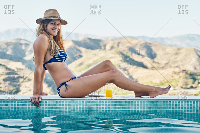 Full body side view of happy slim tanned young female in bikini and hat sitting with glass of fresh fruit juice on poolside against mountainous landscape  and looking at camera