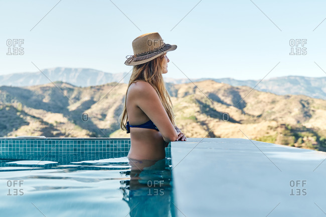 Side view of unrecognizable slim female in swimwear and hat standing in swimming pool and admiring mountainous landscape during summer vacation