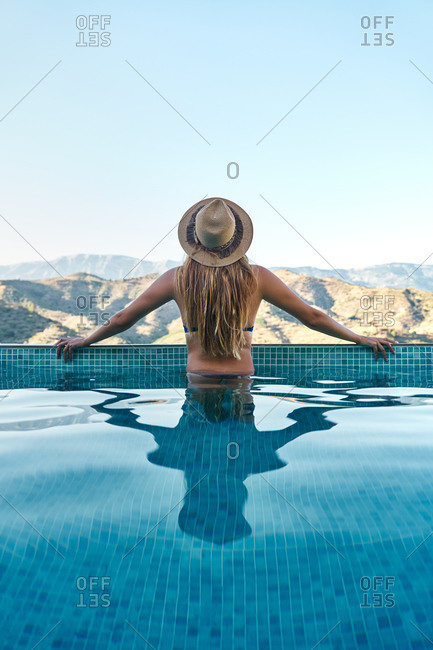 Back view of unrecognizable slim female in swimwear and hat standing in swimming pool and admiring mountainous landscape during summer vacation
