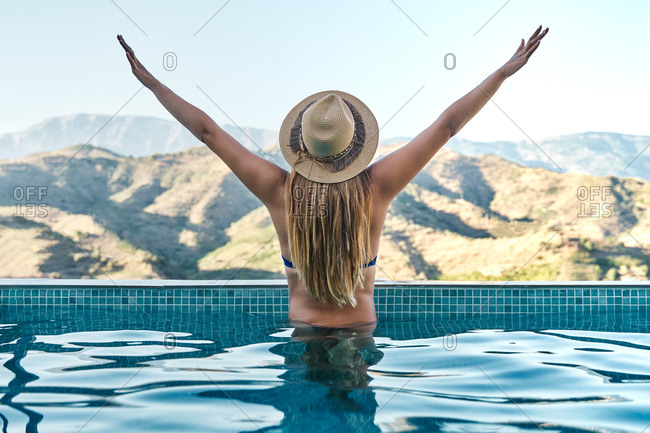 Back view of unrecognizable slim female in swimwear and hat outstretching arms in swimming pool and admiring mountainous landscape during summer vacation