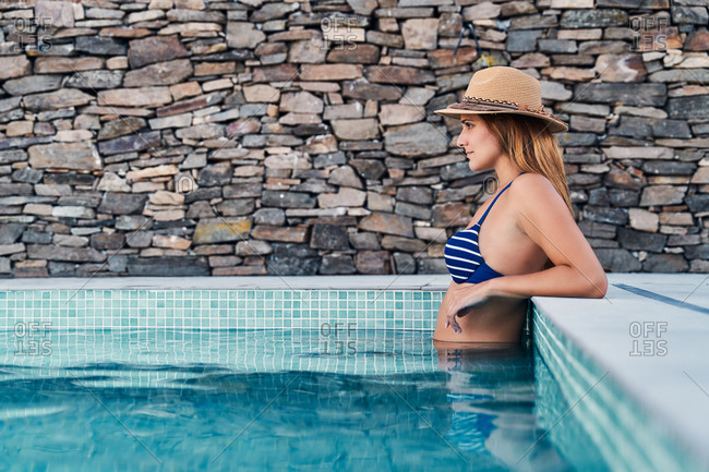 Side view of unrecognizable slim female in swimwear and hat standing in swimming pool during summer vacation