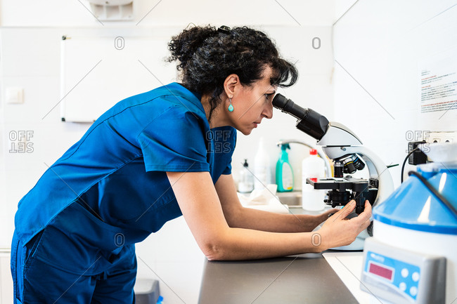 Female doctor looking through modern microscope placed on table in lab of modern clinic