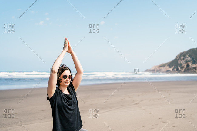 Young female in sportswear standing in Tree pose with arms up while practicing yoga on sandy beach against waving sea with sunglasses