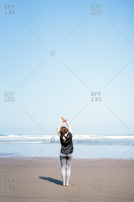 Full body back view of unrecognizable barefooted female in sportswear walking on wet sand towards waving sea with arms raised