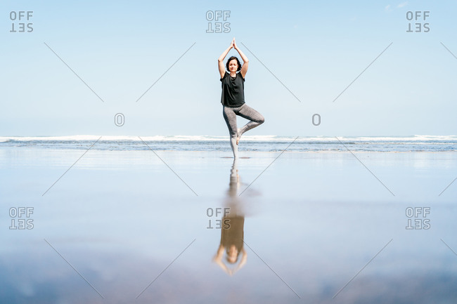 Full body young female in sportswear standing in Tree pose with arms up while practicing yoga on sandy beach against waving sea with eyes closed