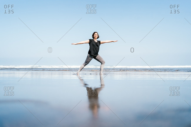 Full body side view of young female in sportswear practicing Warrior yoga asana while standing on wet sand near waving sea with eyes closed