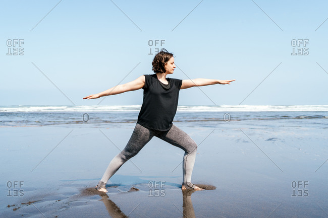 Full body side view of young female in sportswear practicing Warrior yoga asana while standing on wet sand near waving sea