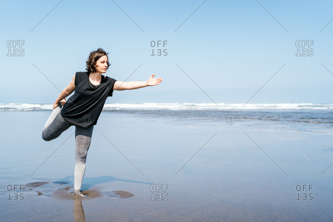 Full body side view of young female in sportswear practicing yoga asana while standing on wet sand near waving sea