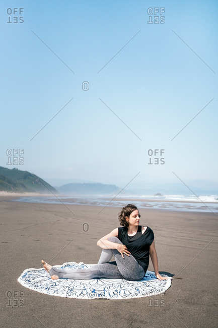 Full body young female in sportswear doing Half Lord of the Fishes variation while practicing yoga on sandy seashore with eyes closed