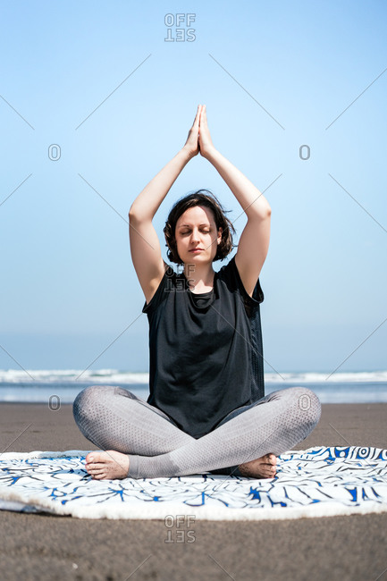 Full body young female in sportswear doing meditation while practicing yoga on sandy seashore