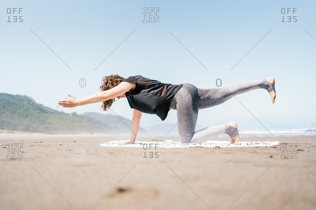 Side full body young female in sportswear practicing yoga on sandy seashore with eyes closed