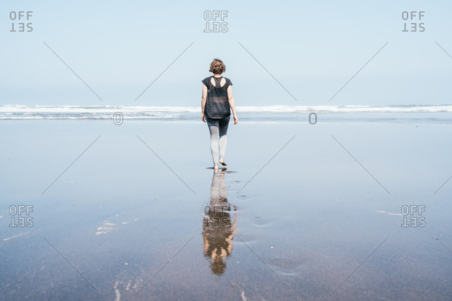 Full body back view of unrecognizable barefooted female in sportswear walking on wet sand towards waving sea