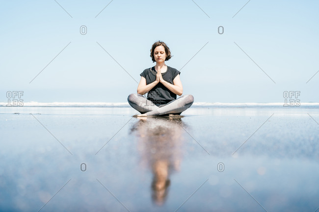 Full body young female in sportswear doing meditation while practicing yoga on sandy seashore with eyes closed