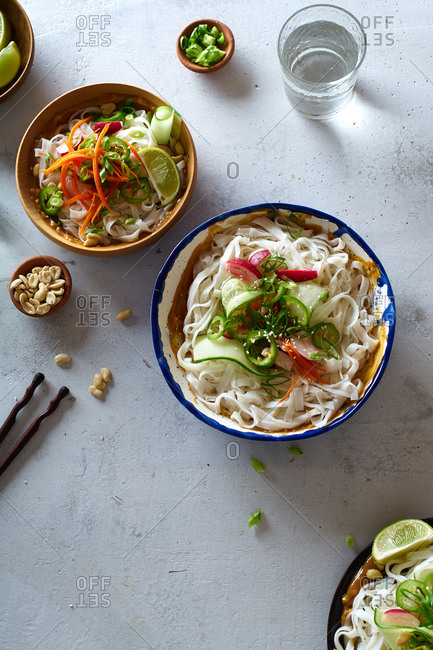 Healthy lunch with vegan rice noodle salad made with fresh vegetables, lime and peanut sauce and a glass of water
