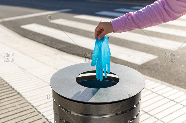 Female hand throwing out a protective glove into the trash can of the street. Coronavirus or Covid-19 waste concept