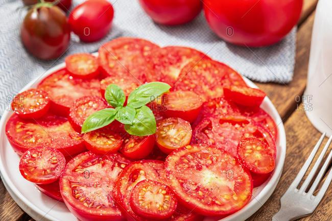 Tomato salad and basil leaves on plate. Mediterranean food