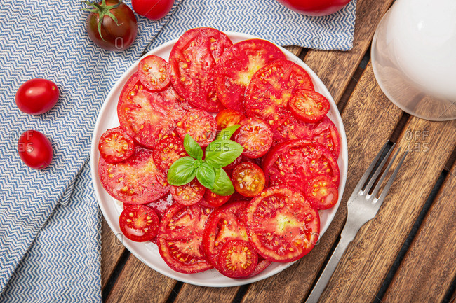 Top view of Tomato salad and basil leaves on plate. Mediterranean food