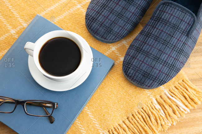 Male home slippers, coffee, book and wool blanket. Home relaxing in wintertime concept