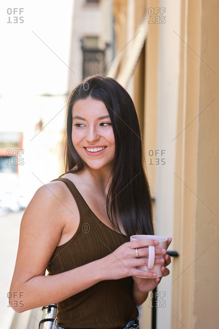 Side view of tender female in casual clothes standing on balcony with cup of fresh coffee while enjoying morning and looking away