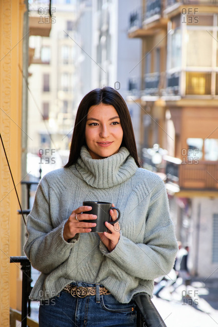 Tender female in warm sweater and with cup of hot beverage standing on balcony and observing street while enjoying weekend