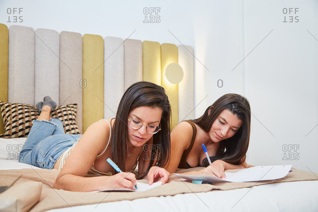 Clever female students lying on bed and writing notes on paper while doing homework assignment together