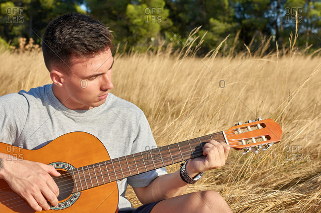 Young talented male guitarist sitting in dried meadow and playing acoustic musical instrument on sunny day