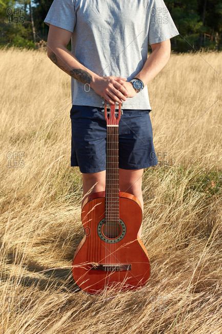 Unrecognizable male musician standing with guitar in dry meadow on sunny day in summer