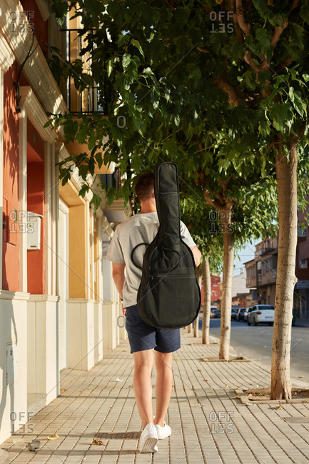 Back view of young male walking along pavement on sunny day with guitar and looking away