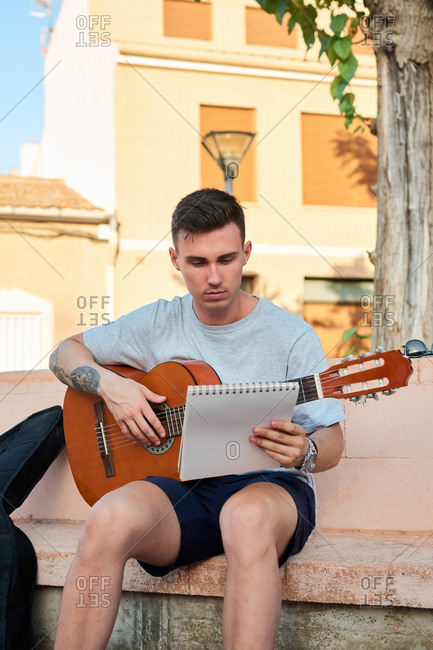 Creative male musician sitting on stone bench on street and reading notes while preparing for playing guitar