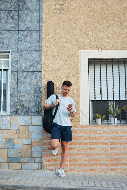 Content male musician with guitar in case standing near urban building and reading messages on social media via cellphone