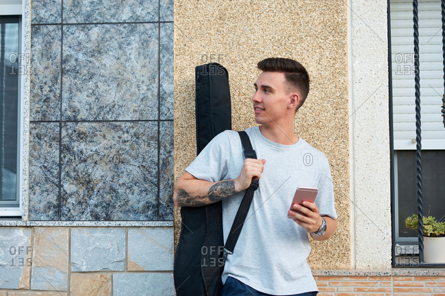 Content male musician with guitar in case standing near urban building with smartphone and looking away