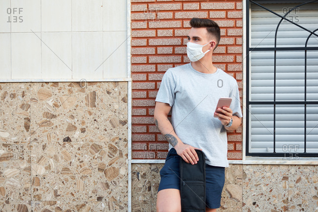 Serious male wearing medical mask standing near building in city and browsing mobile phone while looking away during coronavirus outbreak