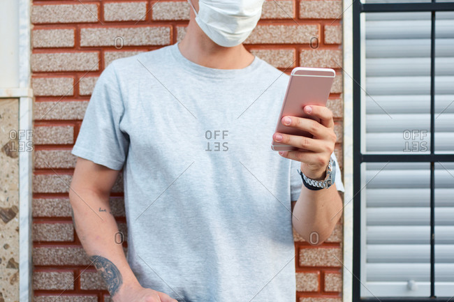 Crop male wearing medical mask standing near building in city and browsing mobile phone during coronavirus outbreak