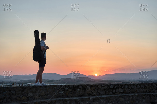 Side view of unrecognizable male guitarist standing with musical instrument in case on stone fence and admiring magnificent sundown in mountains