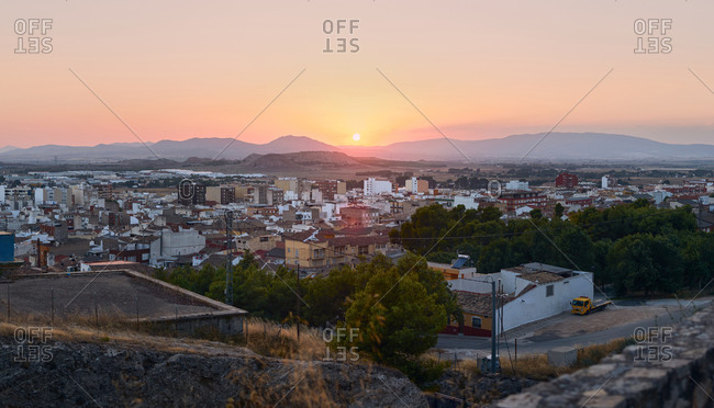 Spectacular scenery of town with old buildings and mountain ridge under sunset sky in evening