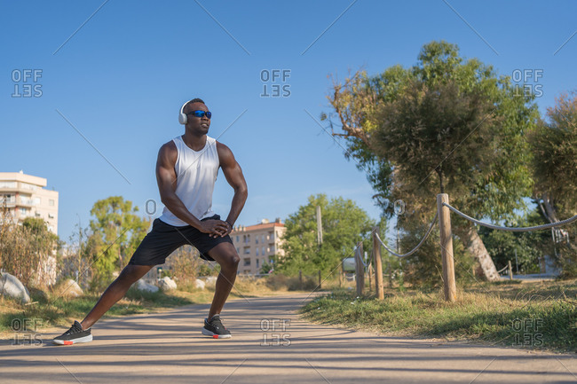 Full body of young muscular African American sportsman in headphones and sunglasses doing stretching exercise while preparing for jogging in city park in summer day