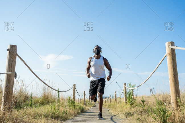 Low angle full body of strong muscular African American male athlete in headphones and protective mask running on narrow fenced path in countryside